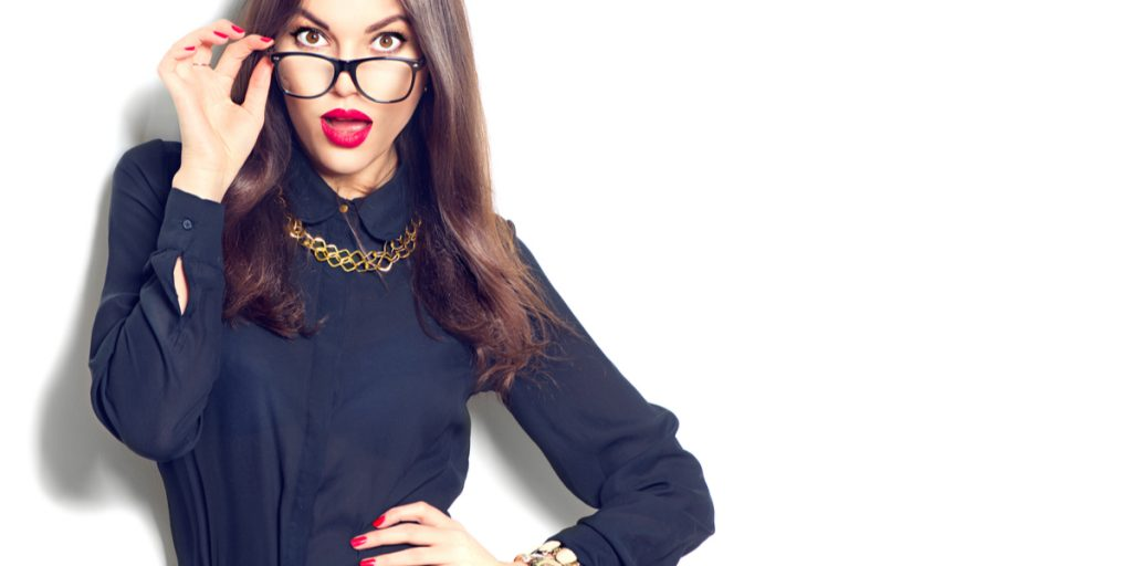 Brunette wearing business clothes and black reading glasses in front of white background