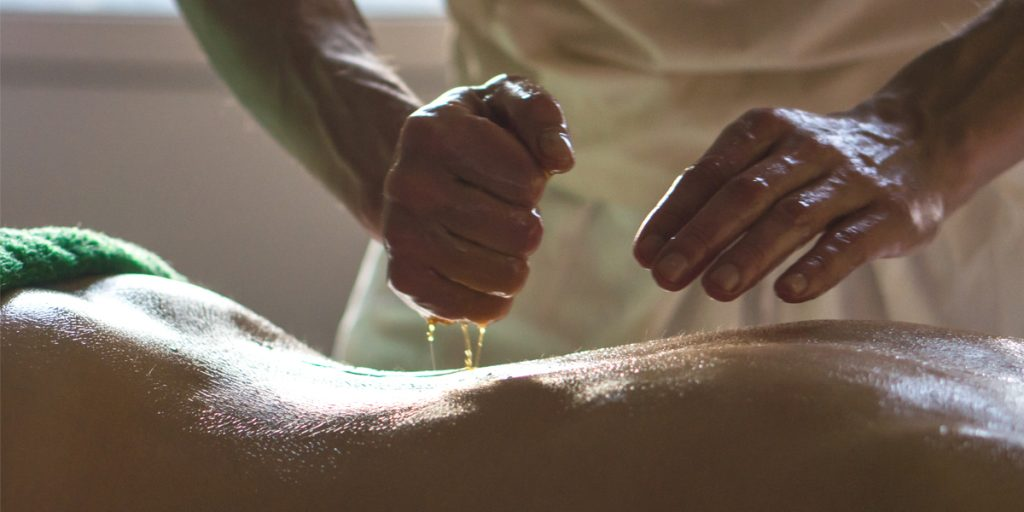 Man dripping massage oil on a woman's bare back