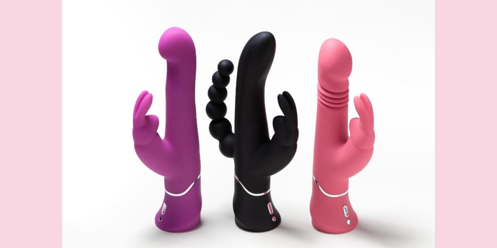 Three rabbit vibrators lined up, purple rabbit, black triple stimulator and pink thrusting rabbit