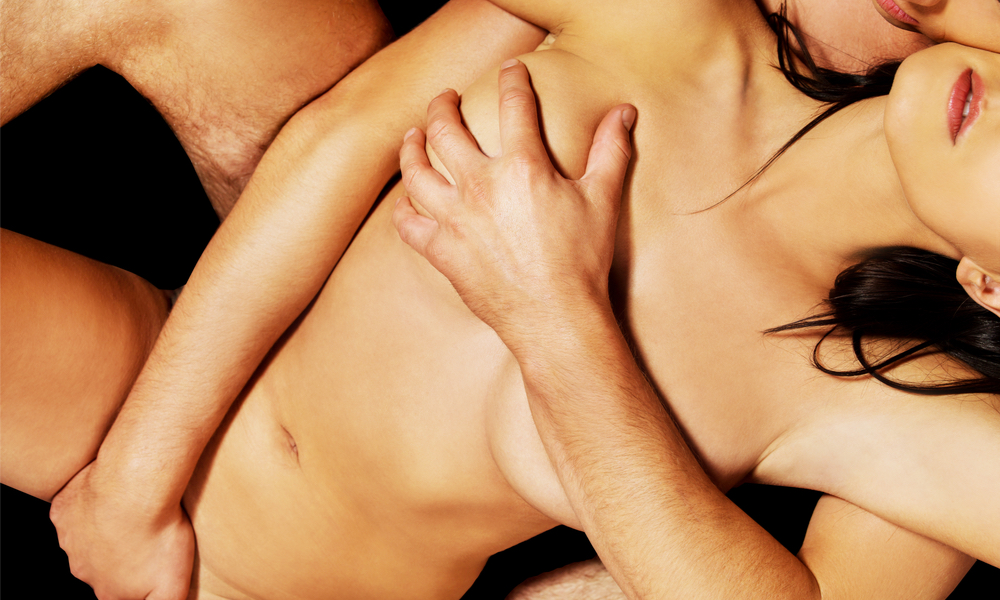 woman laying in from of a man who has his arm covering her breasts and his other hand on her pubic area
