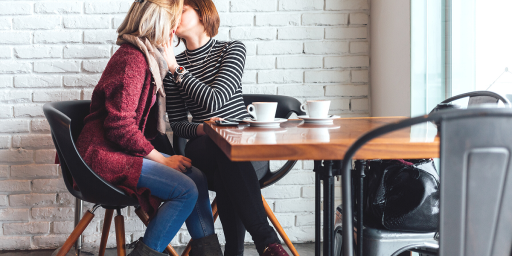 two women sitting in a coffee shop / cafe kissing